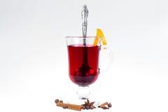 Glas hete overwogen wijn met appelen en sinaasappelen, kruidnagels en vanillestokken op een witte achtergrond De hete drank van K Stock Afbeelding