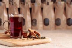 Glas hete thee Houten lepel met droge theebladen Ambachtdocument pak met venster voor losse thee De ruimte van het exemplaar stock afbeeldingen