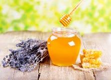 Glas Honig mit Bienenwabe und lavander blüht lizenzfreie stockfotos