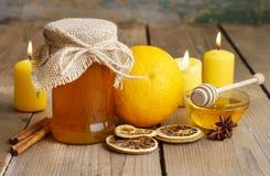Glas Honig, Orangen und Kerzen auf Holztisch stockfoto