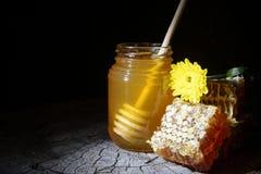 Glas Honig und Bienenwaben auf einem hölzernen Hintergrund Stockfotos