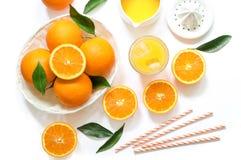 Glas jus d'orange met ijsblokjes en sinaasappelen op witte hoogste mening worden geïsoleerd die als achtergrond Stock Foto