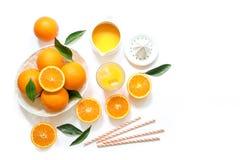 Glas jus d'orange met ijsblokjes en sinaasappelen op witte hoogste mening worden geïsoleerd die als achtergrond Stock Afbeelding