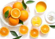 Glas jus d'orange met ijsblokjes en sinaasappelen op witte hoogste mening worden geïsoleerd die als achtergrond Royalty-vrije Stock Afbeelding