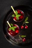 Glas Kirschsaft auf schwarzem Behälter Lizenzfreies Stockfoto