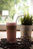 Glas koffie met sommige bonen op de lijst met installatie Stock Afbeeldingen