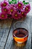 Glas Kognak und Blumen lizenzfreie stockfotos