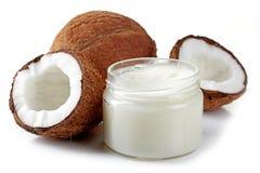 Glas Kokosnussöl und frische Kokosnüsse Stockfotografie