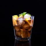 Glas kola met ijs, munt en citroen op zwarte achtergrond Stock Fotografie