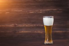 Glas koud bier op een bruine houten achtergrond stock foto