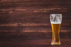 Glas koud bier op een bruine houten achtergrond stock fotografie