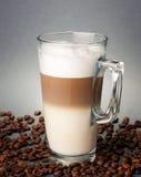 Glas latte macchiato auf den Kaffeebohnen stockbilder
