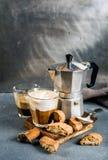 Glas lattekoffie op rustieke houten raad, cantuccikoekjes en pot van staal de Italiaanse Moka, grijze achtergrond Royalty-vrije Stock Afbeeldingen