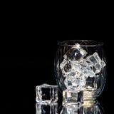 Glas lokalisiert auf schwarzem Hintergrund mit Eiswürfeln Lizenzfreie Stockfotos