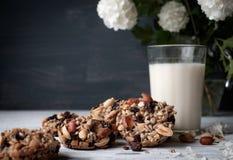 Glas melk en koekjes van noten en rozijnen wordt gemaakt die Royalty-vrije Stock Afbeeldingen