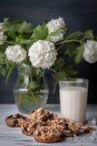 Glas melk en koekjes van noten en rozijnen wordt gemaakt die Stock Fotografie
