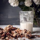 Glas melk en koekjes van noten en rozijnen wordt gemaakt die Royalty-vrije Stock Foto's