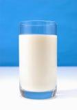 Glas melk op blauw Stock Foto