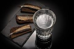 Glas met alcohol en voorgerecht met sprot en brood op steenschotel stock foto