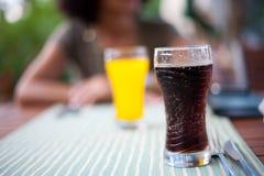 Glas met cokes en dame op achtergrond Stock Foto's
