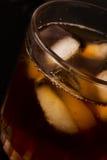 Glas met donker vloeibaar hoogtepunt met ijsblokjes Stock Foto