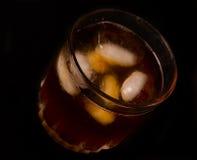 Glas met donker vloeibaar hoogtepunt met ijsblokjes Royalty-vrije Stock Foto's