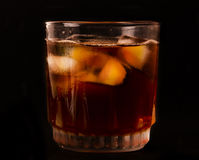 Glas met donker vloeibaar hoogtepunt met ijsblokjes Stock Afbeelding
