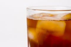 Glas met donker vloeibaar hoogtepunt met ijsblokjes Stock Foto's