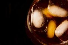 Glas met donker vloeibaar hoogtepunt met ijsblokjes stock fotografie