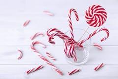 Glas met het riet van het Kerstmissuikergoed op een witte houten lijst stock afbeelding