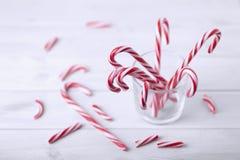 Glas met het riet van het Kerstmissuikergoed op een witte houten lijst stock fotografie