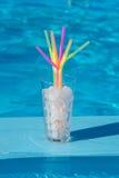 Glas met ijs en stroijs dichtbij de pool Stock Foto
