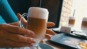 Glas met koffie latte, met gesorteerde kleur van donker bruin aan melkachtig wit Mooie latte met groot schuim in koffie stock video