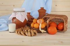 Glas met melk en vers fruit in een rieten mand op de achtergrond van ceramisch vaatwerk Gezond, gezond voedsel Royalty-vrije Stock Afbeeldingen