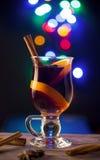 Glas met overwogen wijn op donkere achtergrond met lichten Stock Afbeelding