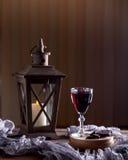 Glas met rode wijn Dichtbij gebroken chocolade Lantaarn met een candl Royalty-vrije Stock Foto