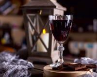 Glas met rode wijn Dichtbij gebroken chocolade Lantaarn met een candl Royalty-vrije Stock Afbeeldingen