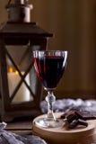Glas met rode wijn Dichtbij gebroken chocolade Lantaarn met een candl Royalty-vrije Stock Afbeelding