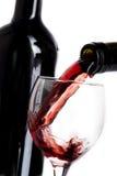 Glas met rode wijn en fles met rode wijn op wit wordt gegoten dat Stock Afbeeldingen