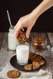 Glas met verse melk en eigengemaakte chocoladeschilferskoekjes over een houten lijst royalty-vrije stock afbeelding