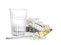 Glas met water en een hoop van tabletten, pillen stock afbeelding