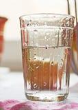 Glas met water en waterdalingen op het stock fotografie