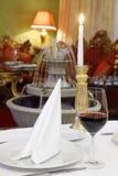 Glas met wijn en kaars bij lijst Stock Foto's