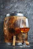 Glas met witte wijn voor het proeven en houten vat met kurketrekker in donkere kelder stock foto's