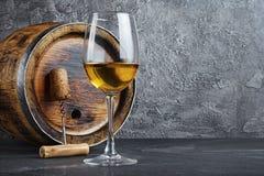 Glas met witte wijn voor het proeven en houten vat met kurketrekker in donkere kelder stock fotografie