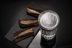 Glas met wodka en voorgerecht met sprot en brood stock afbeelding