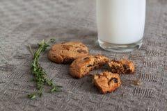 Glas Milch, Kekse, Thymian auf dem Tisch Stockfotos