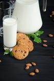 Glas Milch mit Plätzchen und Mandeln stockfotografie