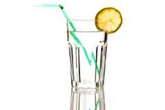 Glas mineraalwater met groene stro en citroen Stock Foto