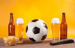 Glas mit Bier und Fußball nahe Fernsehdirektübertragung Lizenzfreies Stockbild